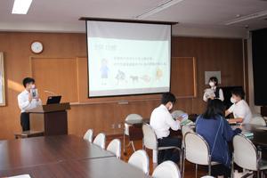 プロジェクト副リーダーの村上彰太さんがツアーに使用するガイドブックについて紹介している様子